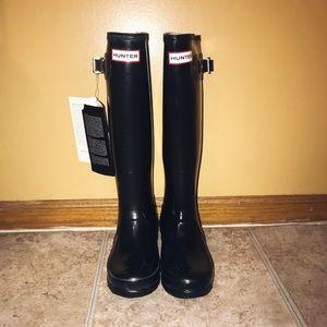 Tall glossy black hunter boots
